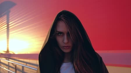 boho : Slowmotion - portrait of amazing mystical female with long hair, looking in to camera with a strict look in red background. Youth Urban lifestyle.