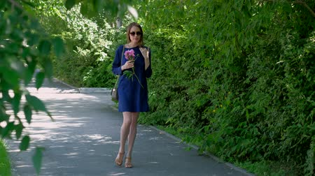 kabelka : A young woman in a blue dress and sunglasses walking in the city Park. Lady walking down the alley with a pink peony flower Dostupné videozáznamy