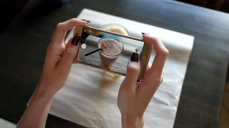 blogger : Female hands photographing coffee cocktail in cafe by smartphone