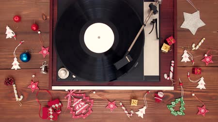 винил : Top view - Old vintage good looking turntable playing music with vinyl on wooden background with christmas decoration. 4k Uhd. Christmas concept. Стоковые видеозаписи