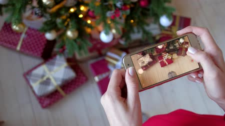 x mas : Beautiful woman photographing on smartphone christmas tree with new year gifts at home. X-mas, winter holidays and people concept. Shot from the first person. 4k uhd. Stock Footage