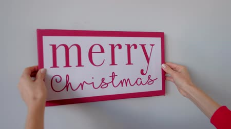 poste de sinalização : Close up - womens hands hang a sign with a red inscription merry Christmas on a white wall. X-mas, winter holidays concept. 4k uhd.