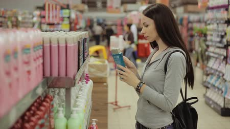şampuan : Girl chooses the shampoo on the shelves in the store