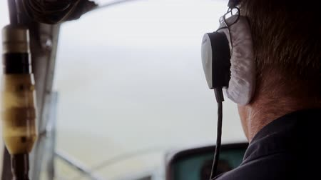 pilot in command : Pilot with earphones inside helicopter