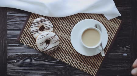 xícara de café : Man Stirs Sugar in a Cup of Coffee, Two Donuts on a Black Wooden Table, Top view