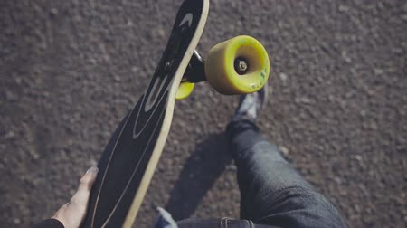 ilk : Close up of longboard in the hands of a man in a sneakers