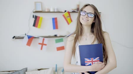 nyelv : Portrait of teen student smiling over flags background. Concept of lessons and learning of foreign languages