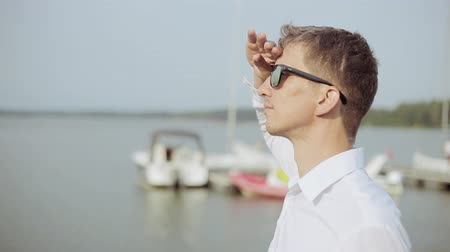 looking far away : A young man in sunglasses standing at the beach and looking far away