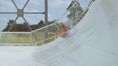 double happiness : Two beautiful girls having fun on the water slide in a water park. Slow motion. Stock Footage
