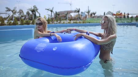 inflável : Two girls communicate in the pool near the inflatable circle in the water park Vídeos
