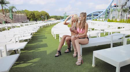 pięta : Two seductive girls with lollipops are sitting on deck chairs and laughing Wideo