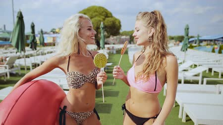inflável : Two attractive sexy girlfriends with lollipops talk on empty sunbeds background