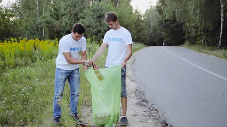 dobrovolník : Two young male volunteers collect empty plastic bottles in a forest near a road Dostupné videozáznamy