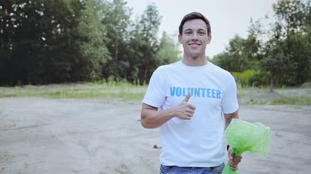 segítség : Smiling young man in volunteer t-shirt gesturing thumb up and looking at camera