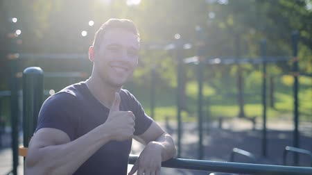 gest : Smiling athlete young man gesturing thumb up and smiling on sports playground