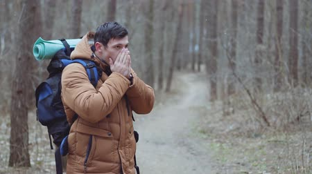 deep autumn : Man tourist blowing on hands, cold weather. Autumn or winter day. Outdoor Stock Footage