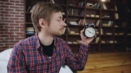 punctuality : Young man student surprised shows the time on the clock