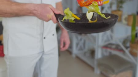 az yağlı : Chef cooking fresh vegetables in frying pan slow motion