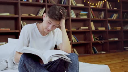 unalom : Young teen student tired and sleeping after so much studying for school, man holding book for reading