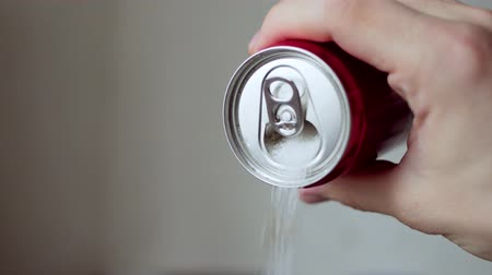 édesség : Man hand holding soda drink can pouring sugar stream - unhealthy drink concept