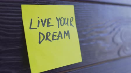 dopisní papír : Live your dream written on yellow paper sticker notes over wooden background
