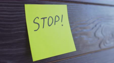 emlékeztető : Word Stop written on yellow paper sticker notes over wooden background