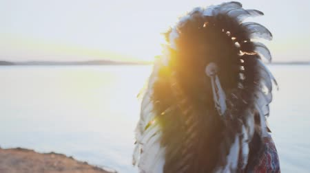 native american culture : Portrait of young girl in costume of American Indian with feather hat roach at sunset slow motion
