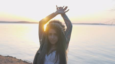 головной убор : Portrait of shamanic young girl with Indian feather hat roach at the beach on sunset slow motion Стоковые видеозаписи