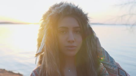 головной убор : Close up portrait of young girl with Indian feather hat roach at the beach on sunset slow motion Стоковые видеозаписи