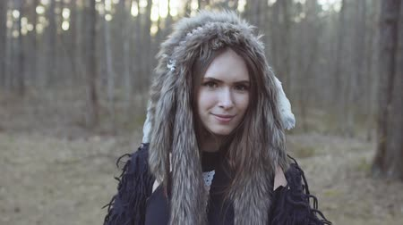 племя : Portrait of young teen girl in costume of American Indian with feather hat roach in forest slow motion Стоковые видеозаписи