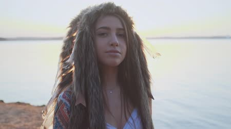 native american culture : Portrait of young dramatic girl in costume of American Indian with feather hat roach at sunset slow motion
