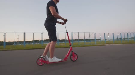 кроссовки : Close-up of young man riding kick scooter at evening