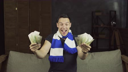 賭け : Handsome euphoric man winning a betting. Man with money celebrate win a bet