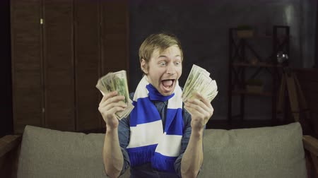piyango : Portrait of young sports fan with white blue scarf holding a lot of money. Man winning a betting Stok Video