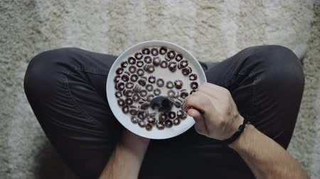 musli : Man holding bowl with chocolate cereal, top view. Healthy eating concept