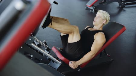 quadriceps : Sporty Young Man Doing Leg Press On Machine In Gym