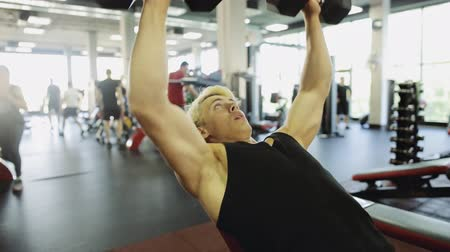 biceps : Blonde man with dumbbells flexing muscles in gym - sport, fitness, bodybuilding concept