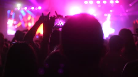 on the phone : Silhouette hands of audience crowd people use smart phones enjoying the concert. Stock Footage