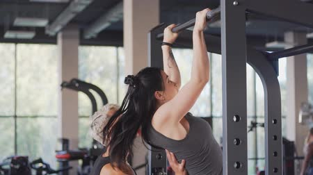 pulling up : Young woman with her personal trainer doing pull ups on horizontal bar