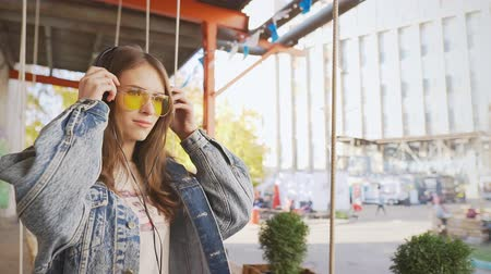 tonları : Hipster girl in sunglasses having fun and listens to music in the headphones Stok Video