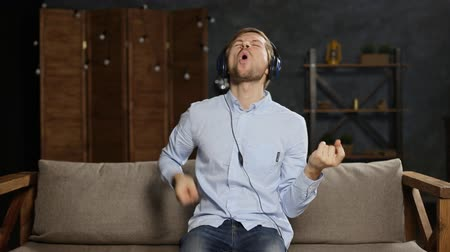invisible : Young man in headphones listening to music and playing on invisible air guitar