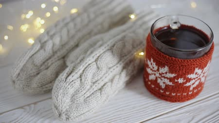 lights up : Close up of warm mittens and knitted cup decoration. Christmas composition on a vintage wooden background Stock Footage