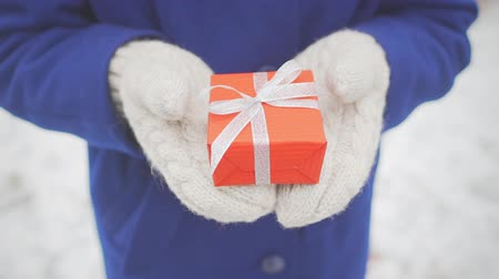 knitted gloves : Woman hands holding red christmas gift in knitted mittens