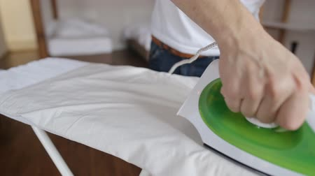 biscate : Close up of young man ironing clothes on ironing board at home