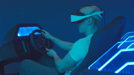 interaktif : Young Man Gamer Wearing Virtual Reality Headset Plays Video Game Racing Simulator With Wheel