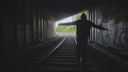 balanceamento : Man alone walking away on the railroad. Teenager balancing on train rail track in urban background