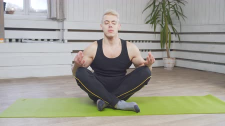 kapalı : Young man in sporty outfit doing yoga and meditating on an exercise mat at home