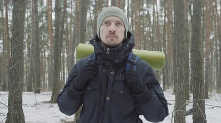 hátizsákkal : Young man hiker with backpack walking in winter forest