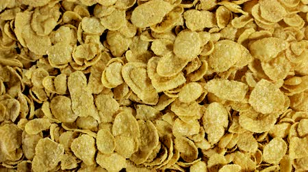 flocos de milho : Pile of cornflakes in stop motion. Cornflakes scattered on a table. Top view. Background and texture