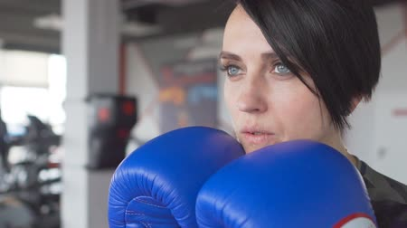 kickbox : Close up portrait of a serious female boxer with gloves inside a boxing ring. Woman with short hair style in gym